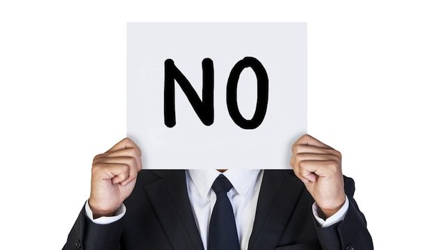 A guy holding up a placard that says No