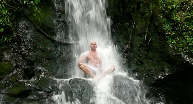 Man sitting at the bottom of waterfall